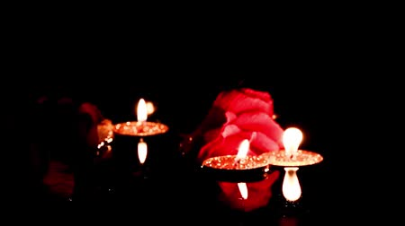 vegetativo : the flame of the wax candle lights the decorative flowers of the rose on the surface of the water