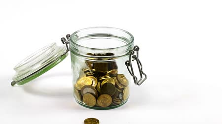 adomány : The metal coins falling into an open glass jar as a symbol of the accumulation of money