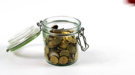 pensão : The metal coins falling into an open glass jar as a symbol of the accumulation of money