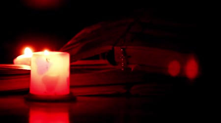 biblia : The pages of old books, the cross and the candle flame Wideo