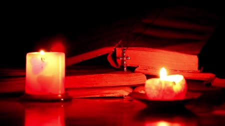 kereszténység : The pages of old books, the cross and the candle flame Stock mozgókép