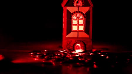 buy gold : falling metal coins to a house with lighted windows as a symbol of a mortgage