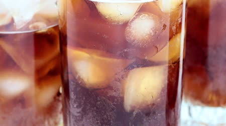 cola : a glass with a carbonated drink and pieces of ice