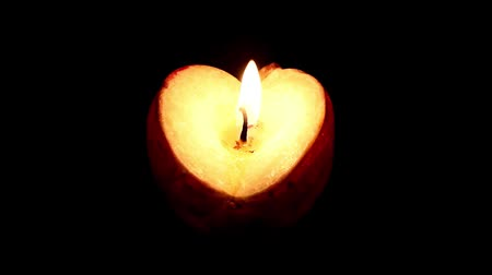 memory : fluttering flame of a wax candle on a dark background