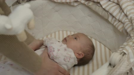 babygirl : The girl takes the child out of the crib Stock Footage