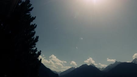 nearly : Timelapse of clouds moving on blue skies behind mountains and trees Stock Footage