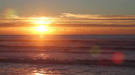 curto : Sunset over the ocean with small waves, clouds and beautiful red sunlight and reflections on the water surface