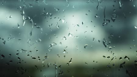 mosqueado : Focus on digitally generated raindrops that fall on a foggy window during the day when it rains and the background is blurred.