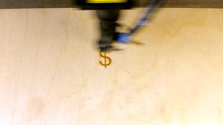гравюра : Laser engraving machining at work.  Beam of laser writing the USA currency sign  on plywood