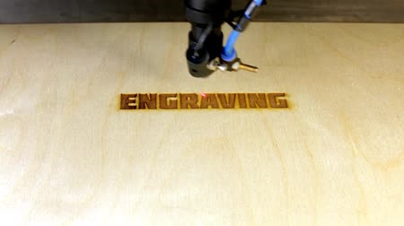 zpracování dřeva : Laser engraving machining at work.  Beam of laser writing word ENGRAVING on plywood