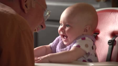 retirement : Grandfather talking with his granddaughter in high chair Stock Footage