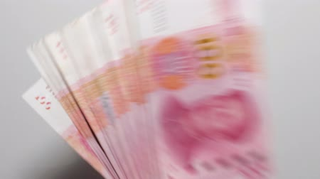 renminbi : Big pile of 100 yuan banknotes falling on the white table, chinese currency, slow motion