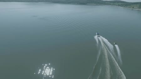 trubky : Aerial drone view of tube riding behind the boat on the lake on sunny day