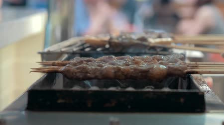 koyun eti : Close-up of frying pieces of meat in the grill on wooden sticks. Asian cuisine.