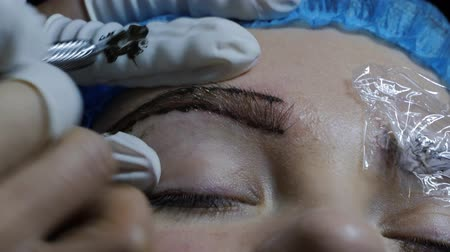 microblading : Close-up of cosmetologist making microblading procedure. Stock Footage