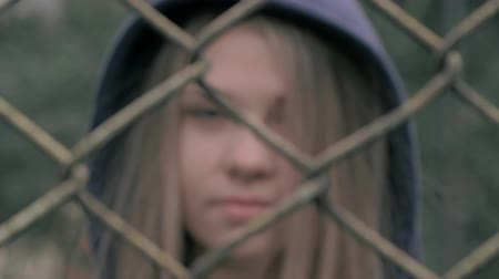 hapis : Portrait of moody and sad blonde caucasian girl behind the iron fence. Young woman behind metal fence grid jail locked