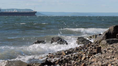 formação rochosa : The waves crashing against the rock on the sea shore, cargo ship on the background Stock Footage