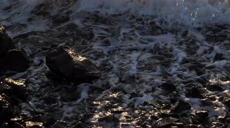 formação rochosa : The waves crashing against the rock on the sea shore on the sunset