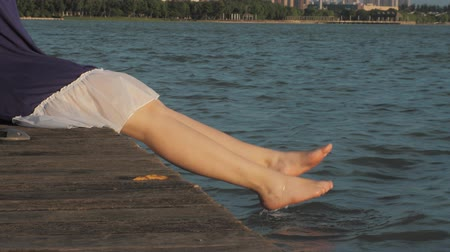 dangle : Girl is sitting on a wooden pier and splashing with his feet in the water.