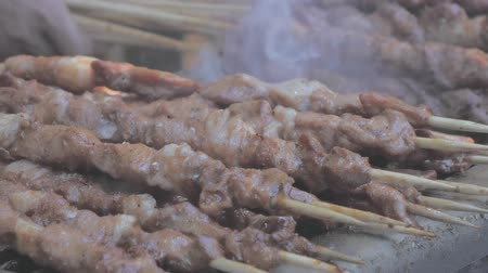 condimento : Close-up of frying pieces of meat in the grill on wooden sticks. Asian cuisine.