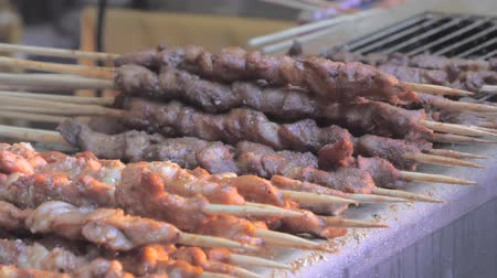 špejle : Close-up of frying pieces of meat in the grill on wooden sticks. Asian cuisine.