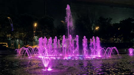 cákanec : Close-up view of beautiful colorful fountain on city street at night.