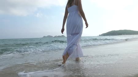 ślady stóp : Girl in white dress walking on the sand beach on sunny day. Slow motion. Wideo