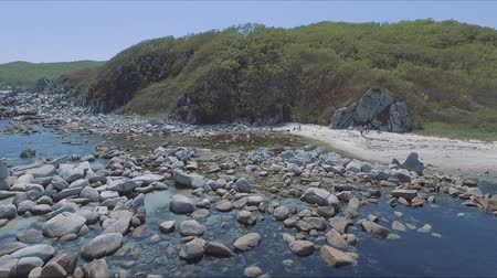 formação rochosa : Aerial shot of coastline bay with the rocks and cliffs. Aerial drone footage of ocean waves washing up on rock at beach. Stock Footage