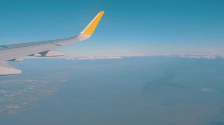 чирок : Airplane flight. View from the window of the plane wing. Airplane flying above the clouds with blue sky. Traveling by air. Travel concept.
