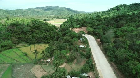 nublado : Aerial view of countryside road passing through the lush greenery and foliage tropical rain forest mountain landscape