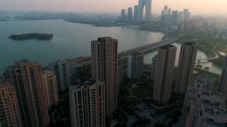 blok mieszkalny : Suzhou, China - April 01, 2019: Aerial shot over residential apartment buildings on sunset. Aerial shot over community apartment complex with modern buisness buildings and lake on the background. Wideo