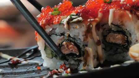 fileto : Close-up of chopsticks holds sushi roll over a plate in restaraunt. Traditional Japanese cuisine.