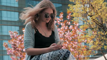 mensajero : Close-up of beautiful young european girl in sunglasses sitting on the street and using smartphone with skyscrapers in the background