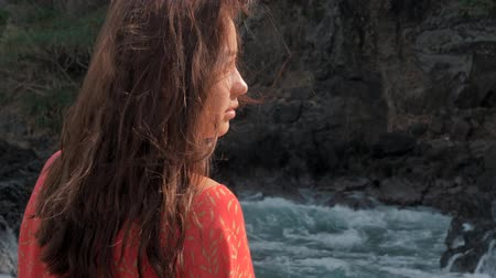 enorme : Close-up view of young girl in red dress standing near storm waves hitting the rocks Young girl looking out to ocean, waves breaking against the stones. Travel concept. Palawan, Philippines.