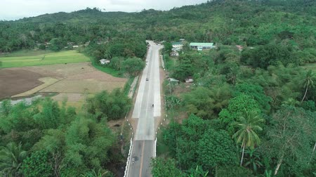 kurmak : Aerial drone shot of concrete road in a small farming community. Aerial view of countryside road. Philippines, El Nido.