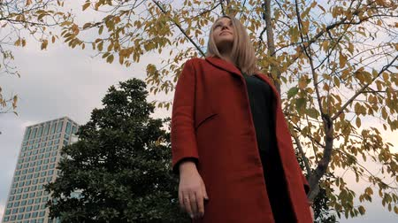 facetime : Young woman in red coat standing in autumn colorful park, enjoying autumn foliage. Stock Footage