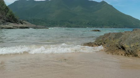 pedregoso : Sea waves water splashing on rocky beach at tropical island. Beautiful sea waves on stony shore. Forest covered mountain on the background. Palawan, Philippines.