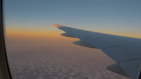 чирок : Airplane flight. Wing of an airplane flying above the clouds with sunset sky. View from the window of the plane. Airplane, Aircraft. Traveling by air.