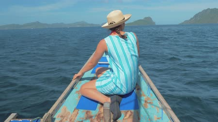 луки : Rear back view of young girl sitting on bow of boat and looking to beautiful nature landscape during trip. Happy woman enjoying summer travel. Vacation or holiday concept. Palawan, Philippines. Стоковые видеозаписи