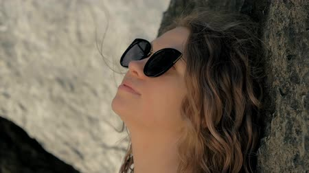 think big : Happy woman in sunglasses resting lean back on mountain at summer day. Relaxing girl leaning back on big stone and enjoying summer day
