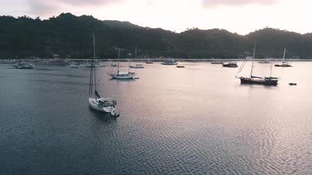 kotvící : Aerial drone view of boats anchored in the bay with clear and turquoise water on the sunset. Boat and yacht in the tropical lagoon. Tropical landscape. El Nido, Palawan island, Philippines. Dostupné videozáznamy