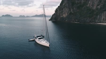 kotvící : Aerial drone view of sailing yacht anchored in the bay with clear and turquoise water on the sunset. Sailing yacht in the tropical lagoon. Tropical landscape. El Nido, Palawan island, Philippines. Dostupné videozáznamy