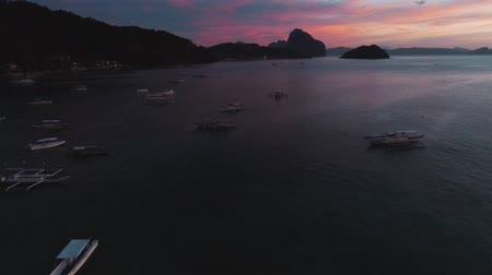 sail rock : Aerial view of boats and yachts in the tropical bay on the sunset. El Nido, Palawan, Philippines. Marine tropical sunset over the sea. Travel concept.