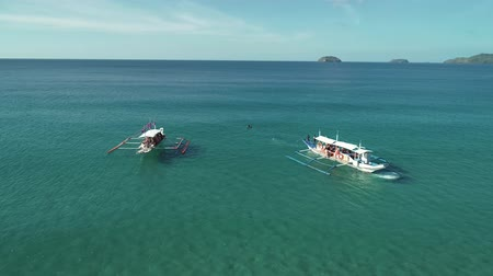 waters : Aerial shot of a two filipino touristic boats floating in turquoise pristine water. Palawan Island, Philippines