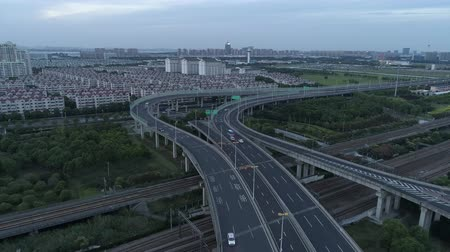 interscambio : Aerial drone view of highway multi-level junction road with moving cars at sunset. Cars are moving on a multi-level road junction The concept of the urban. Suzhou city, China.