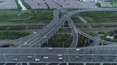 junção : Aerial drone view of highway multi-level junction road with moving cars at sunset. Cars are moving on a multi-level road junction The concept of the urban. Suzhou city, China.