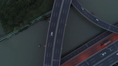 csomópont : Aerial drone view of highway multi-level junction road with moving cars at sunset. Cars are moving on a multi-level road junction The concept of the urban. Suzhou city, China.