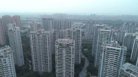 establishing shot : Aerial drone shot over residential apartment buildings on sunset. Aerial shot over community apartment complex in China.
