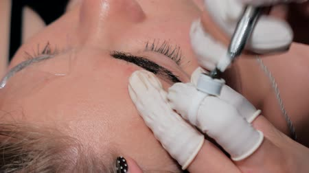 agulha : Close-up of cosmetologist making microblading procedure. Permanent makeup. Permanent tattooing of eyebrows. Cosmetologist applying permanent make up on eyebrows- eyebrow tattoo.