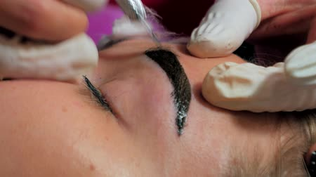 microblading : Close-up of cosmetologist making microblading procedure. Permanent makeup. Permanent tattooing of eyebrows. Cosmetologist applying permanent make up on eyebrows- eyebrow tattoo.